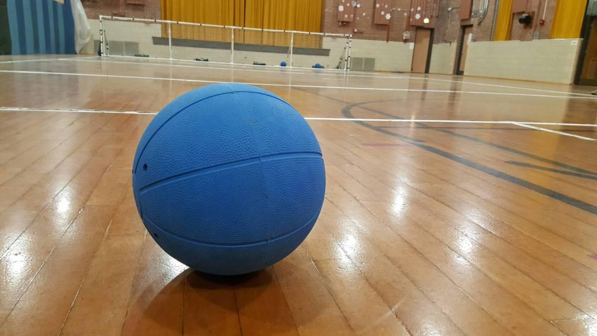 A blue goalball sitting on a gym floor.